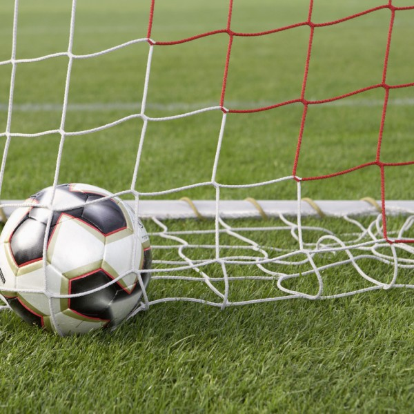 Soccer Ball in Goal Net --- Image by © Royalty-Free/Corbis